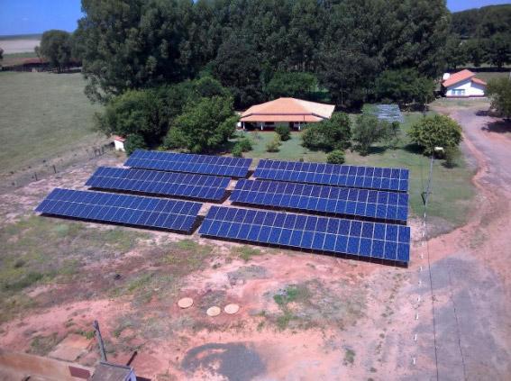 Vista de cima de painéis solares com uma casa atrás em uma área rural. Cogera Energia